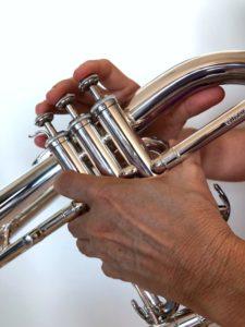 Left hand holding a flugelhorn